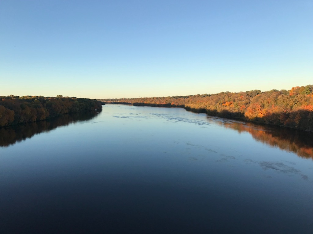 Photo of the Mississippi River at sunset. Fall colors are in full view along both banks. The Lake Street bridge is visible in the distance